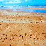 "Photo of beach with ""summer"" written in the sand"
