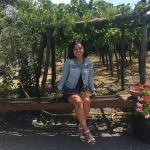 Photo of Elizbaeth sitting in front of a fence at a Vinyard